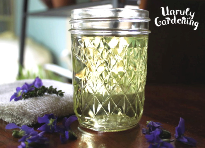 Jar of tea, lightly tinted green, surrounded by scattered violets.