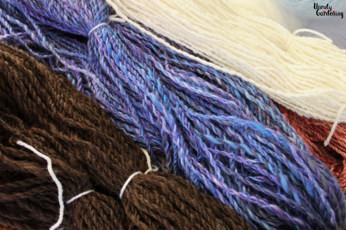 An image of skeined, plied homespun yarn. From bottom left, diagonally up to upper right, there is a skein of brown merino wool yarn, in the middle, a skein of a purple and blue yarn, and lastly, a skein of white angora yarn. A small portion of a pinkish yarn is visible on the right side between the purple and white yarns. All the yarns are tied off with white ties.