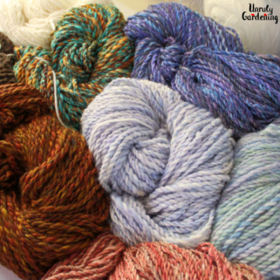 Image is of a box of coiled, handspun yarn of varying colors. The yarn is tied into skins with white yarn.