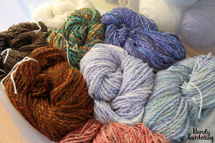 Image is of a box of coiled, handspun yarn of varying colors. The yarn is tied into skins with white yarn- in the background, through the plastic, store-bought yarn can be seen stacked.