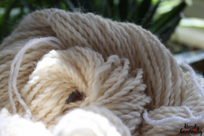 Image of a 2-ply handspun white yarn, loosely coiled. The yarn takes up most of the image, but green plants can be seen in the background.