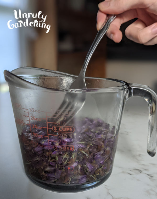 kudzu flowers and boiling water in a glass measuring cup